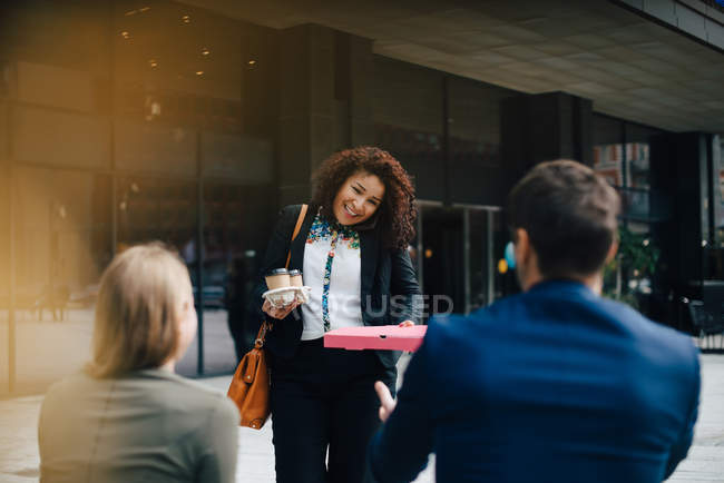 Smiling mid adult businesswoman talking on mobile phone while giving food and drinks to colleagues against cafe — Stock Photo