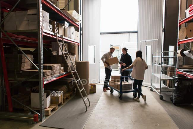 Cotrabajadores femeninos y masculinos que analizan las cajas de la industria - foto de stock