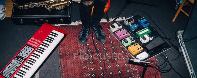Низкая часть музыкант, стоя у музыкальных инструментов на полу в студии — стоковое фото