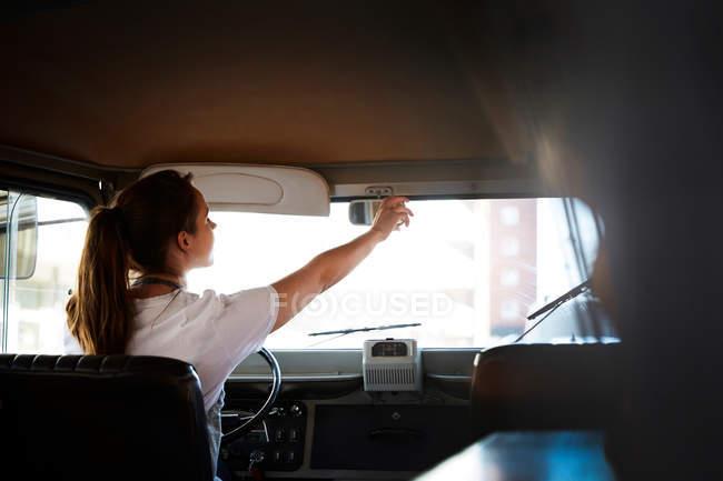 Передній вигляд власниці жіночої статі регулює заднє дзеркало в продовольчій вантажівці. — стокове фото