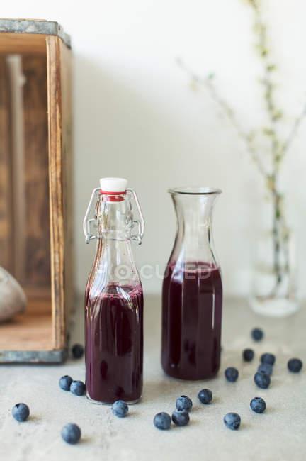 Nahaufnahme der Saft in Glasflaschen mit Heidelbeeren auf Tisch — Stockfoto