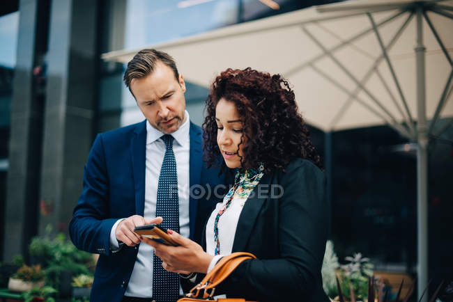 Businessman and businesswoman sharing mobile phone against parasol in city — Stock Photo