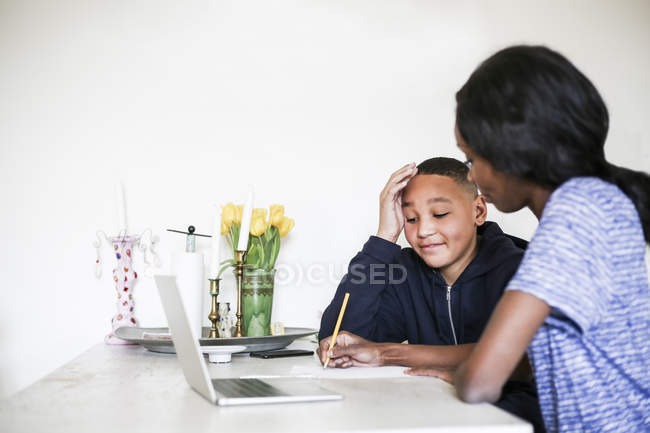 Mother helping son doing homework at dining table — Foto stock