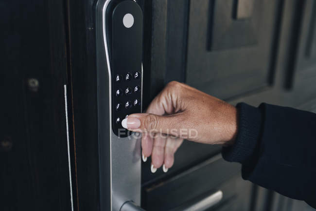 Cropped hand of woman unlocking combination security code on house door — Stock Photo