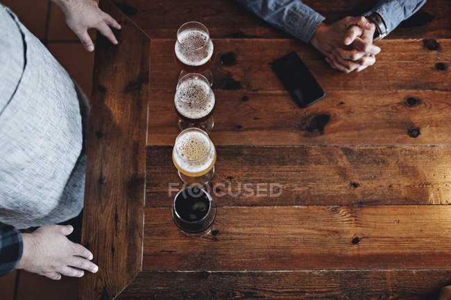 Directly above shot of bartender with various beer glasses by customer at wooden table — Stock Photo