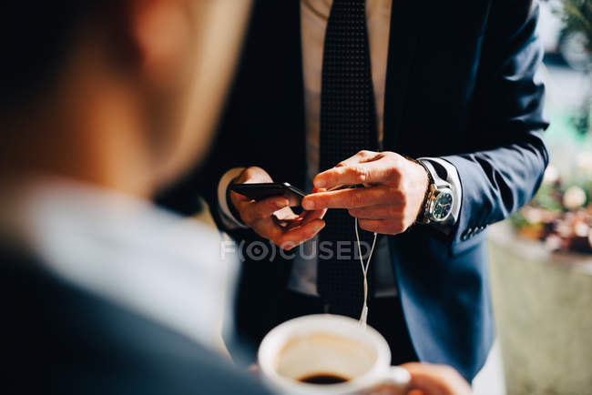 Midsection of businessman using smart phone while standing with colleague drinking coffee at cafe — Stock Photo