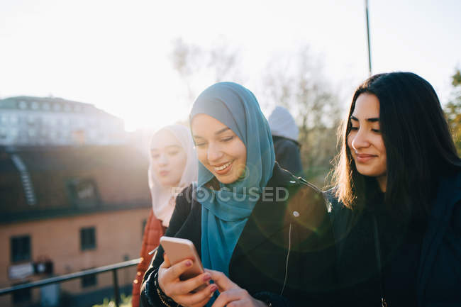 Back lit of smiling young woman using smart phone by female friends in city — Stock Photo