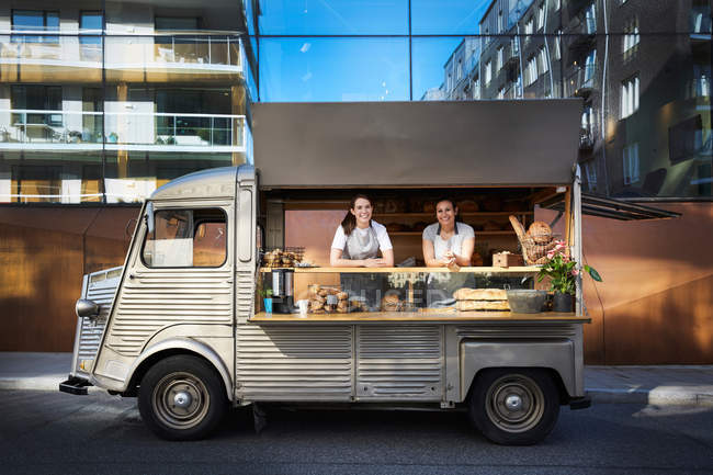 Portrait of female owners in food truck parked on city street against building — Stock Photo