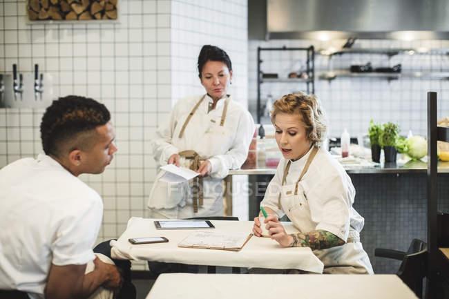 I proprietari multietnici discutono mentre sono seduti a tavola nel ristorante — Foto stock