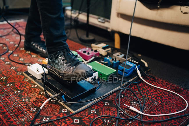 Low section of man using equipment while practicing in recording studio — Stock Photo