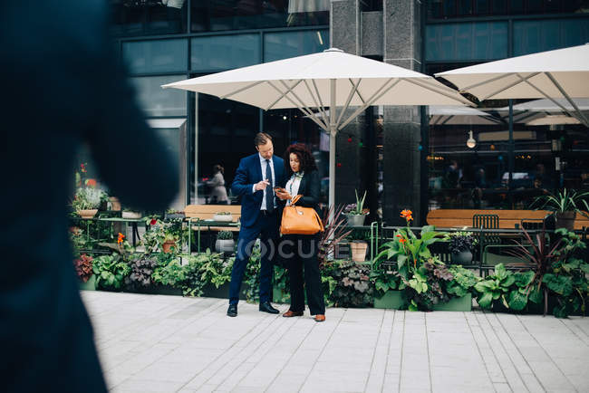 Full length of businessman and businesswoman sharing mobile phone against parasol in city — Stock Photo