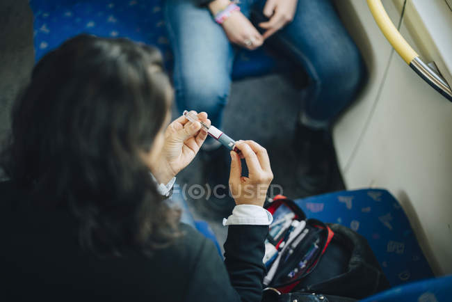 Woman checking injection pen while sitting in train — Stock Photo