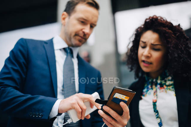 Low angle view of businessman and businesswoman sharing smart phone in city — Stock Photo