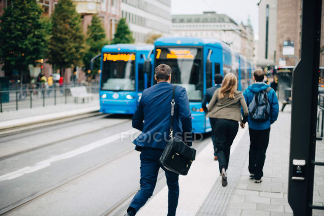 Rear view of people running towards cable car on street in city — Stock Photo