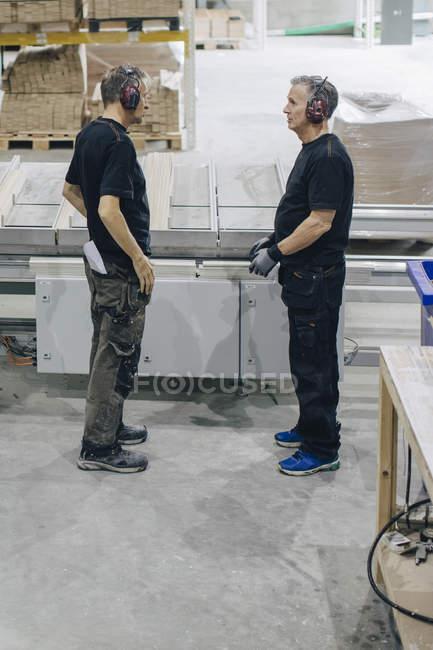 Seitenansicht männlicher Arbeiter, die im Stehen an Maschinen in der Industrie reden — Stockfoto