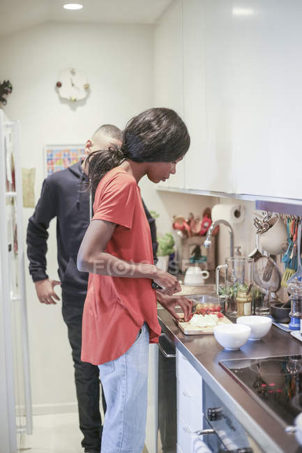 Mulher adulta meada cozinhar comida pelo filho na cozinha em casa — Fotografia de Stock