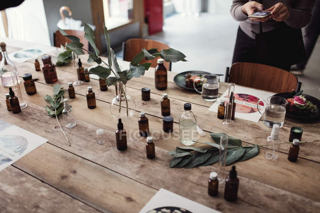 High angle view of various perfume bottles on table by woman photographing at workshop — Foto stock