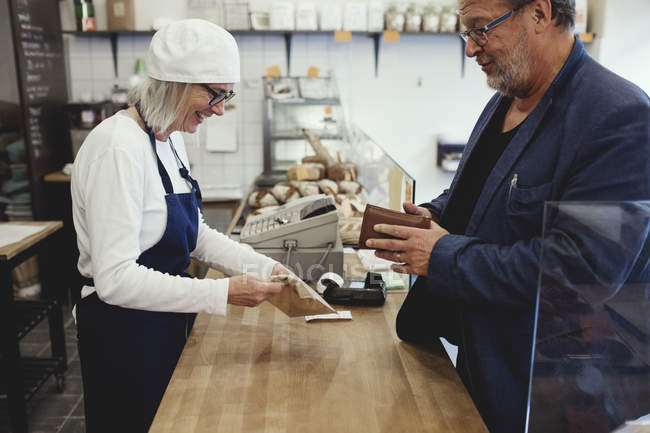 Male customer paying female baker while standing at checkout corner in bakery — Stock Photo