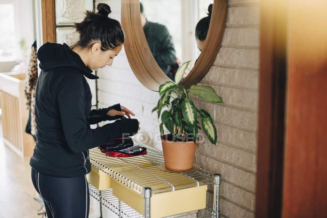 Frau checkt Diabetes-Set, während sie zu Hause vor dem Spiegel steht — Stockfoto