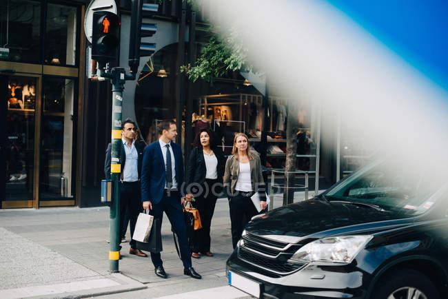 Travailleurs d'affaires multiethniques debout sur le trottoir en voiture contre un bâtiment dans la ville — Photo de stock