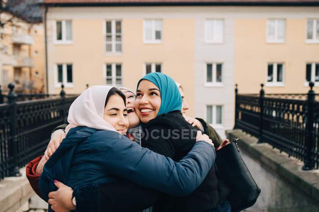 Alegre multi-étnicas amigas musulmanas abrazándose en la ciudad - foto de stock