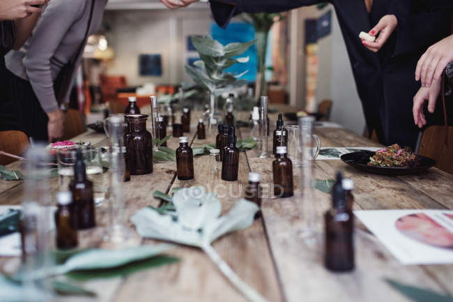 Various perfume bottles on table amidst female coworkers standing at workshop — Stock Photo