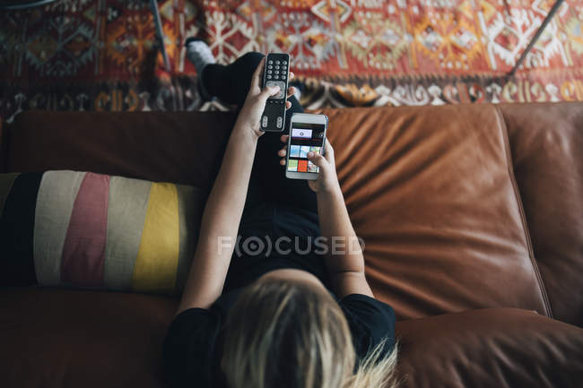 Vue d'angle élevé de l'adolescente utilisant l'application de téléphone et la télécommande tout en s'asseyant sur le sofa regardant la tv à la maison — Photo de stock