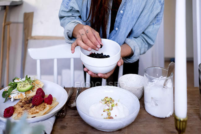 Midsection of woman adding blackberries in yogurt on plate by vase at wooden table — Stock Photo