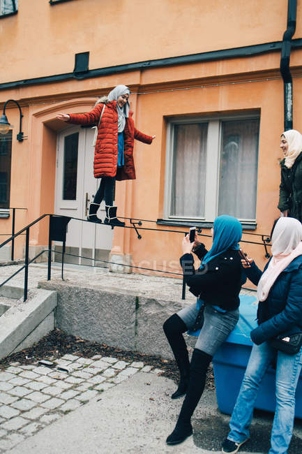 Woman with friends photographing female balancing on railing against building in city — Stock Photo