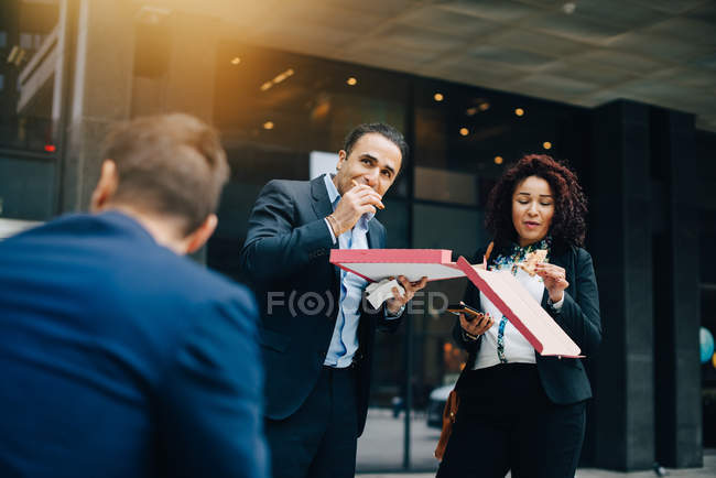 Low angle view of businessman and businesswoman eating pizza against building during lunch — Stock Photo