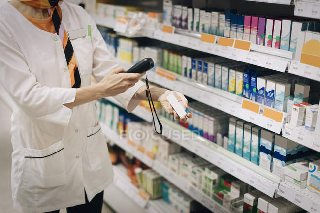 Midsection of female owner using bar code reader on medicine standing by rack at store — Stock Photo