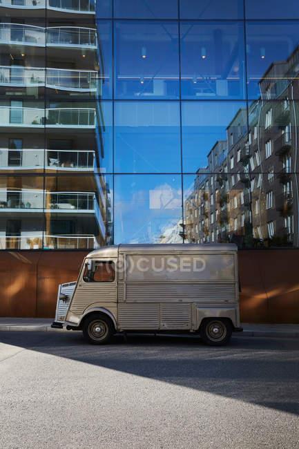 Camion alimentaire garé sur la rue de la ville contre le bâtiment en verre moderne — Photo de stock