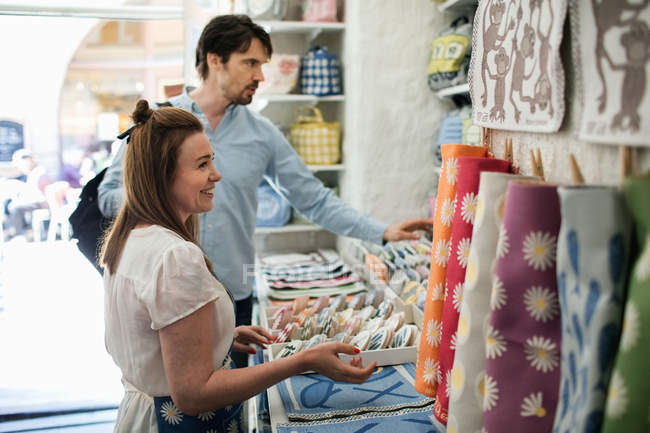 Smiling owner showing fabric swatches to male customer at shop — Stockfoto