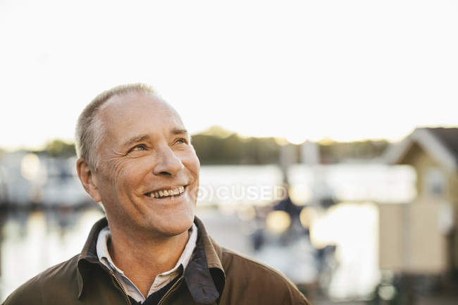 Thoughtful senior man looking up and smiling outdoors — Stock Photo