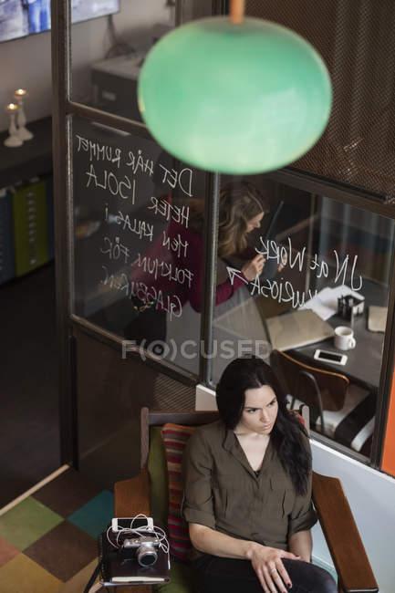 Високий кут зору ділової жінки сидячи за склом в творчому кабінеті — стокове фото