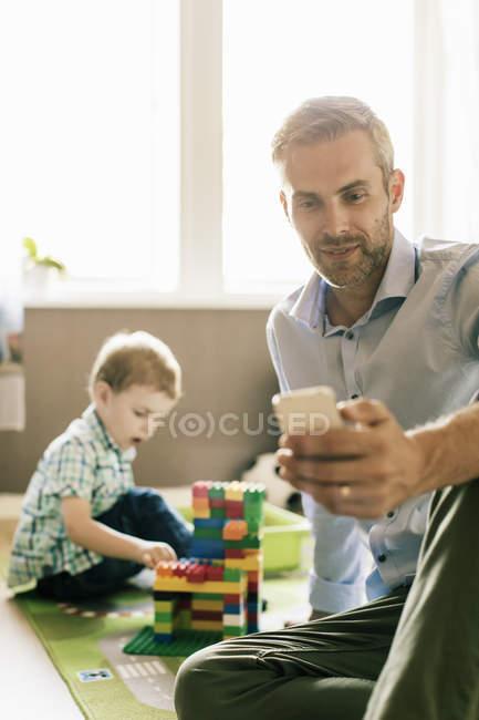 Padre sonriente usando el teléfono mientras el hijo juega con bloques de juguete en casa - foto de stock