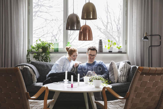 Couple looking in smartphone while sitting on sofa at home — Stockfoto
