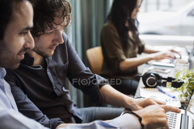 Творчі бізнесмени обговорюють ноутбук в той час як жінка-колега сидить на столі в офісі — стокове фото