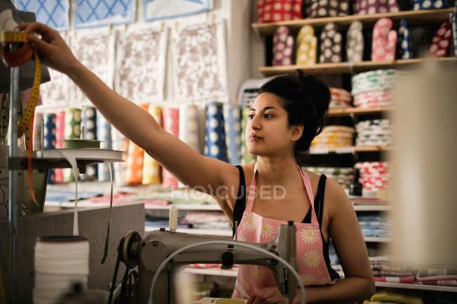 Femme atteignant pour ruban à mesurer lors de la couture textile dans le magasin de tissu — Photo de stock