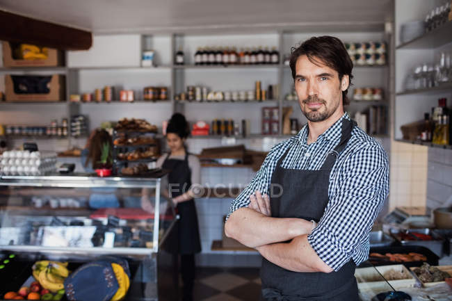 Portrait of confident owner standing with arms crossed against colleague in store — Stockfoto