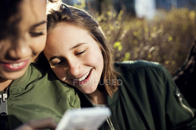 Smiling teenage girl resting with friend while looking at phone on sunny day — Stock Photo