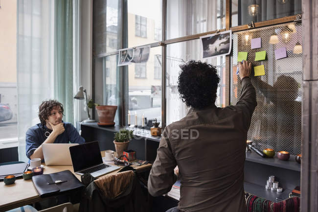 Creative businessmen discussing over adhesive notes in modern office — Stock Photo