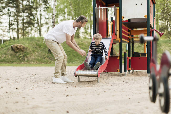 Щасливий батько дивиться на сина грає на слайді на ігровому майданчику — стокове фото