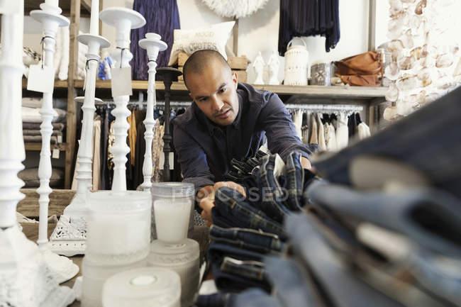 Чоловічий власник організовує джинси на стіл свічками в магазині одягу — стокове фото