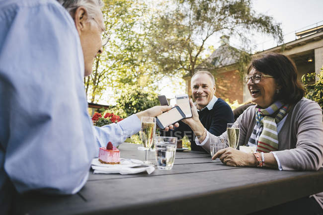 Happy senior friends holding mobile phones at outdoor cafe — Stock Photo