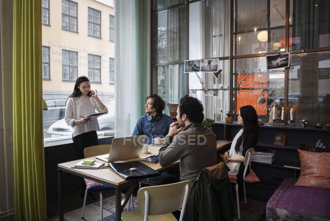 Creative businesswoman sharing ideas with team in modern office — Stock Photo