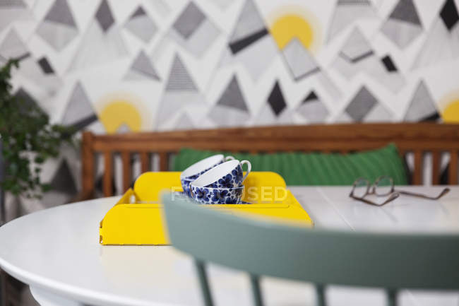 Vista distante de xícaras de chá de cerâmica na bandeja na mesa branca — Fotografia de Stock
