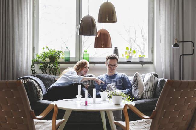 Paar nutzt Technologien, während es zu Hause auf dem Sofa sitzt — Stockfoto