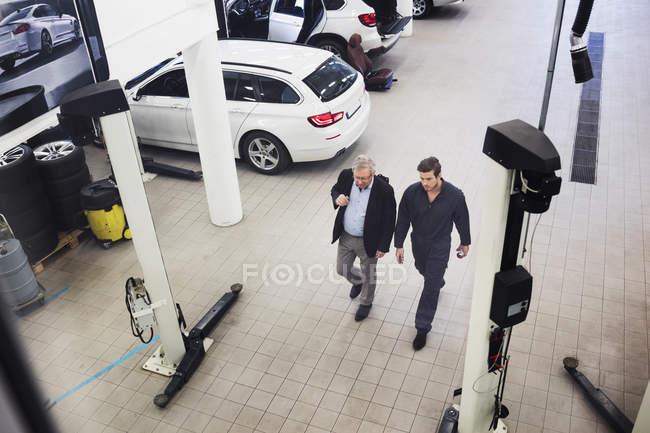 Vue en angle élevé de l'homme âgé discutant avec le mécanicien tout en marchant dans l'atelier de réparation automobile — Photo de stock