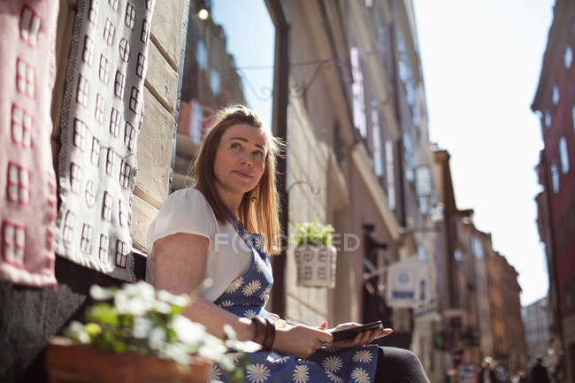 Side view of owner using digital tablet while sitting outside fabric shop — Stockfoto